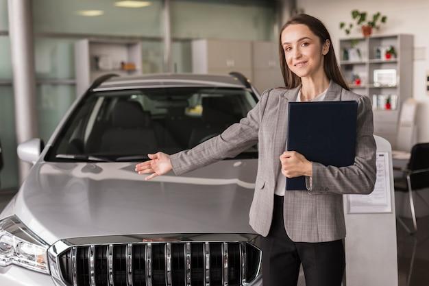 Weiblicher autohändler, der ein auto zeigt