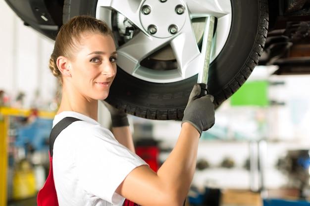 Weiblicher automechaniker, der an aufgebocktem auto arbeitet