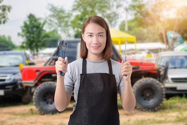 Weiblicher automechaniker und handhalteschlüssel