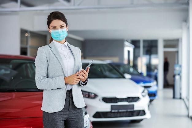 Weiblicher autoverkäufer im anzug mit gesichtsmaske, die im autosalon steht und tablette während des ausbruchs des koronavirus hält.