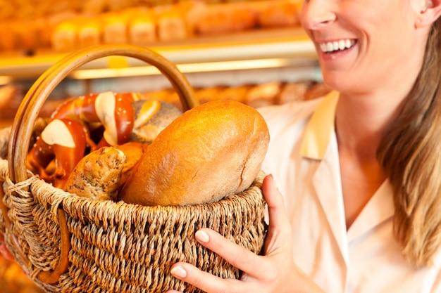 Weiblicher bäcker, der brot durch korb in der bäckerei verkauft