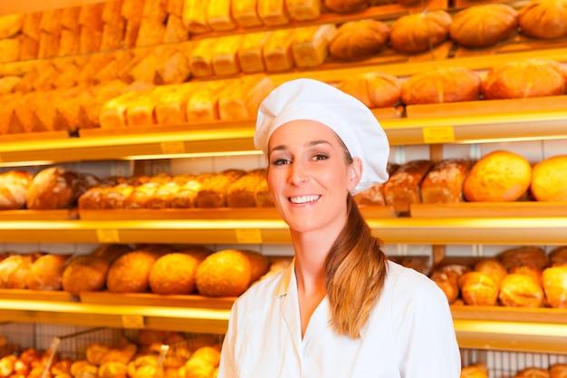 Weiblicher bäcker, der brot in der bäckerei verkauft