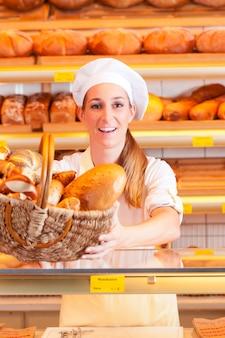 Weiblicher bäcker, der brot in ihrer bäckerei verkauft