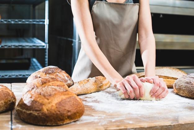 Weiblicher bäcker, der den teig auf holztisch knetet