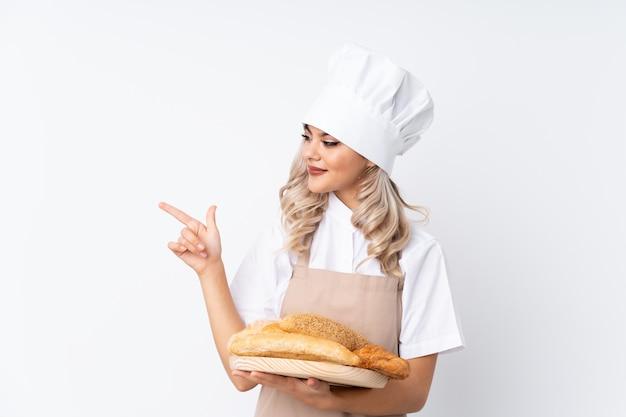 Weiblicher bäcker, der eine tabelle mit einigen broten über dem lokalisierten weißen hintergrund zeigt finger auf die seite hält