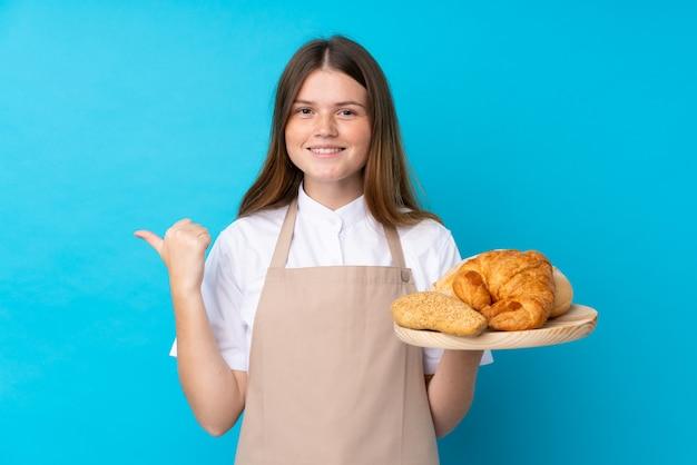 Weiblicher bäcker, der eine tabelle mit einigen broten zeigen auf die seite hält, um ein produkt darzustellen