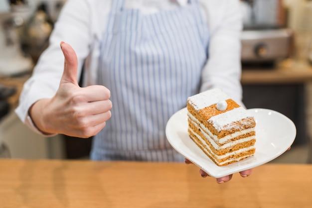 Weiblicher bäcker, der frisches gebäck in der keramischen platte der herzform zeigt daumen herauf zeichen hält