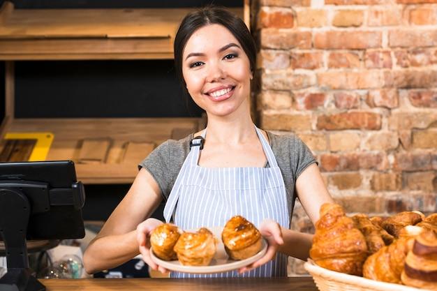 Weiblicher bäcker, der gebackenen süßen blätterteig auf platte an der bäckereikasse zeigt