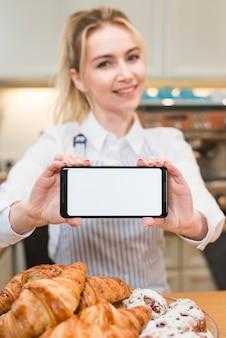 Weiblicher bäcker, der intelligentes telefon mit weißem leerem bildschirm nahe dem gebackenen hörnchen zeigt