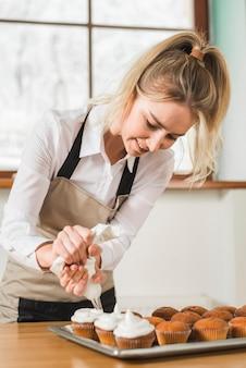 Weiblicher bäcker, der kleinen kuchen mit weißer buttercreme verziert, indem er den puderzucker zusammendrückt