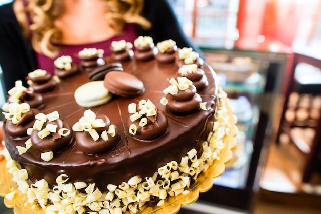 Weiblicher bäcker, der kuchen in den süßigkeiten darstellt
