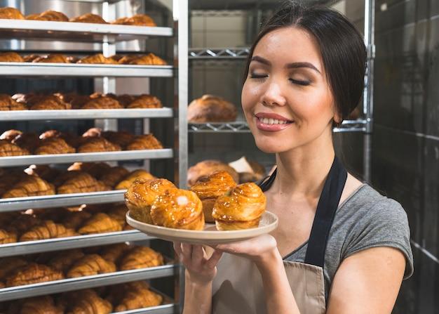Weiblicher bäcker in der bäckerei, die frischen blätterteig auf platte riecht