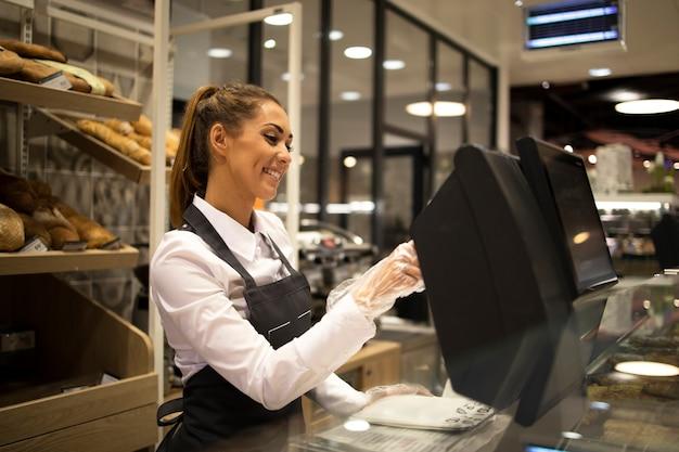 Weiblicher bäckerverkäufer, der am computer arbeitet und brot im supermarkt verkauft