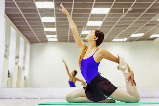 Weiblicher balletttänzer in pointe-schuhen, die auf der matte aufwärmen