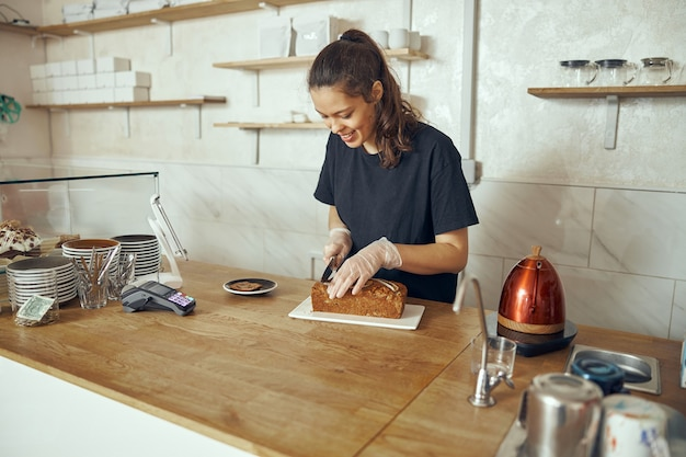 Weiblicher barista am schaufenster mit desserts im café. junger arbeiter des süßwarenladens und des cafés.