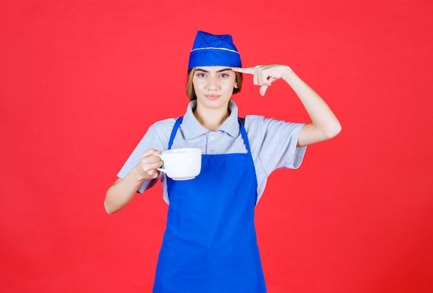 Weiblicher barista, der eine weiße große tasse hält und denkt