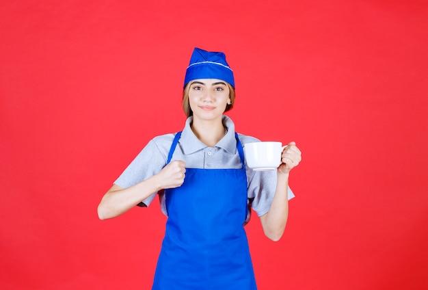 Weiblicher barista, der eine weiße große tasse hält und sich mächtig fühlt