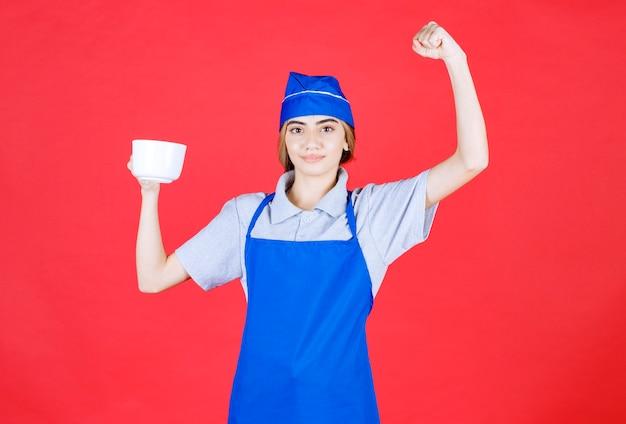 Weiblicher barista, der eine weiße große tasse hält und sich mächtig fühlt Kostenlose Fotos