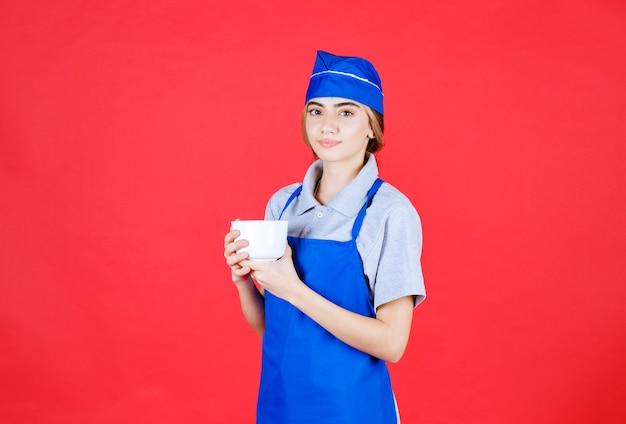 Weiblicher barista, der eine weiße große tasse hält