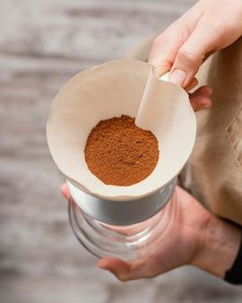 Weiblicher barista, der kaffeefilter über krug hält