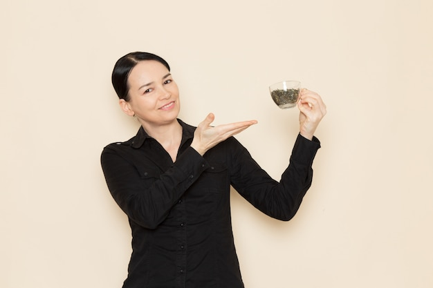 Weiblicher barista in der schwarzen hemdhose, die tasse mit getrocknetem tee an der weißen wand hält