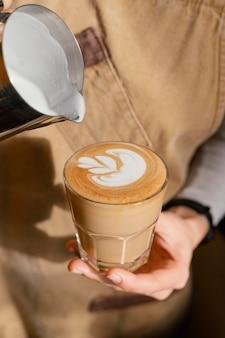 Weiblicher barista mit schürze, die kaffeeglas mit milch verziert