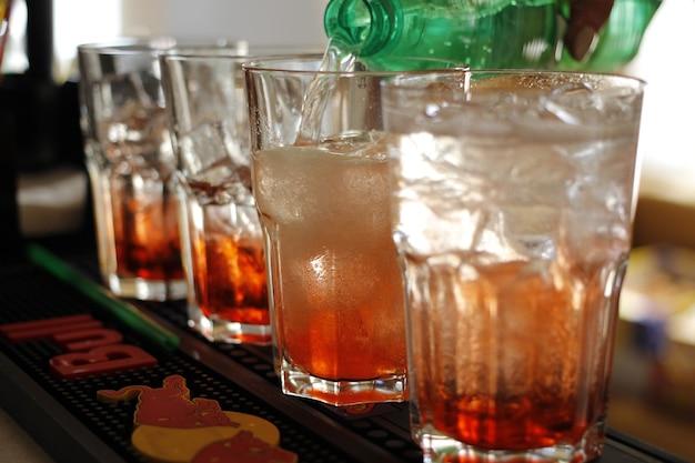 Weiblicher barkeeper, der cocktail mit hinzufügung des roten stiers macht