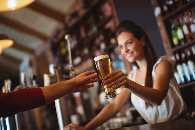 Weiblicher barkeeper, der dem kunden ein glas bier gibt