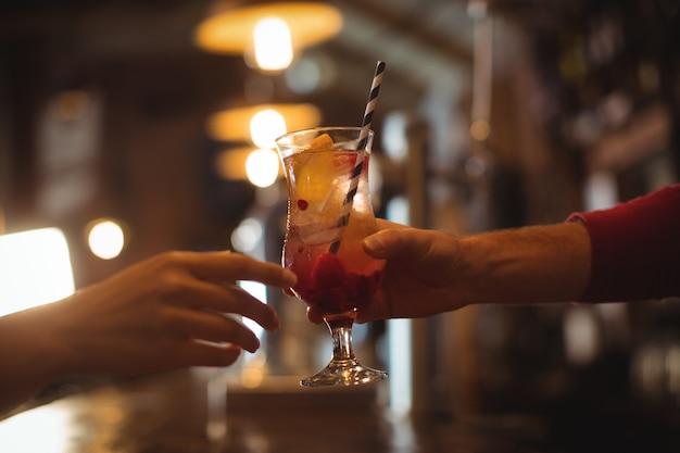 Weiblicher barkeeper, der dem kunden ein glas cocktail gibt