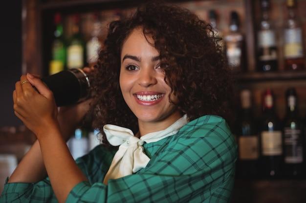 Weiblicher barkeeper, der ein cocktailgetränk im cocktail-shaker mischt