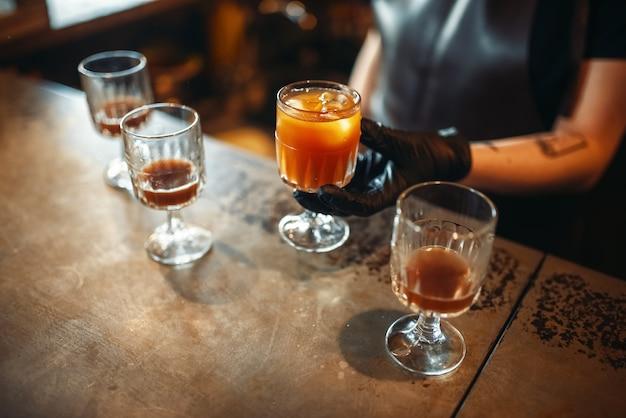 Weiblicher barkeeper, der ein glas mit coctail hält