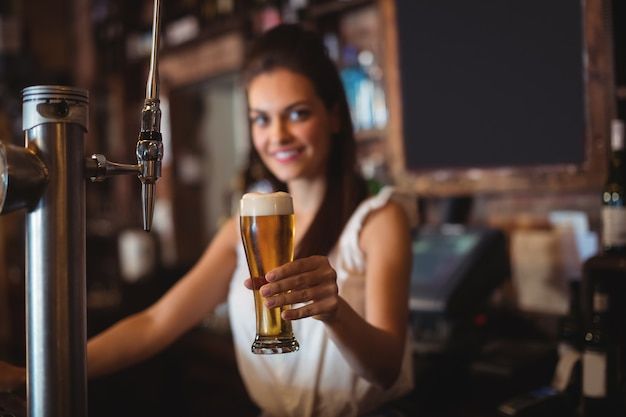 Weiblicher barkeeper, der glas bier hält