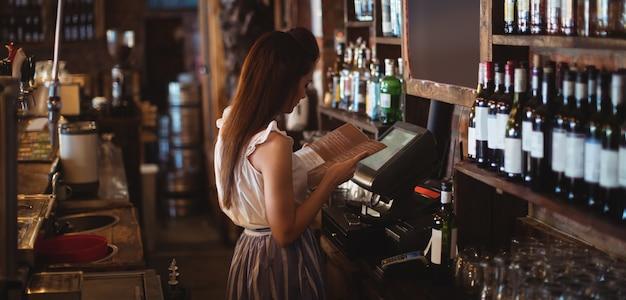 Weiblicher barkeeper, der menü betrachtet