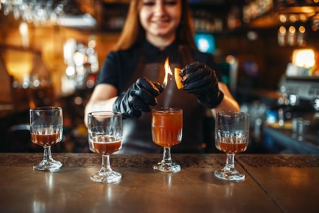 Weiblicher barkeeper, der unter verwendung von feuer coctail macht