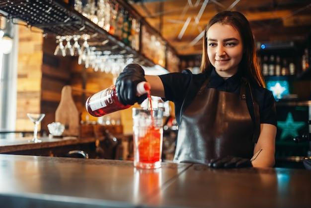 Weiblicher barmann bereitet alkoholischen coctail mit eis vor