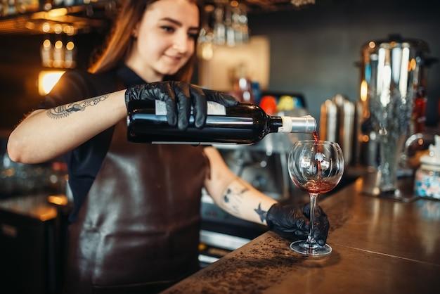 Weiblicher barmann gießt rotwein in ein glas