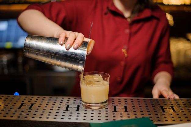 Weiblicher barmixer, der ein frisches cocktail in das glas gießt