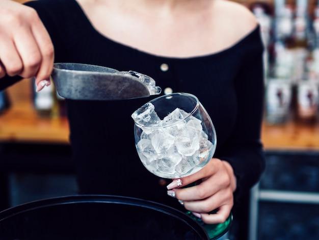 Weiblicher barmixer, der eiswürfel glas hinzufügt