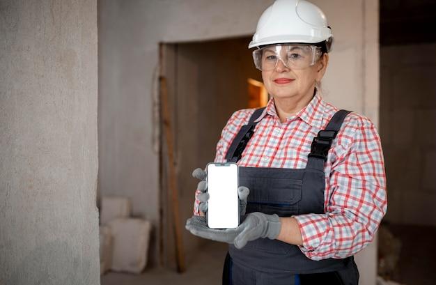 Weiblicher bauarbeiter mit helm, der smartphone hält