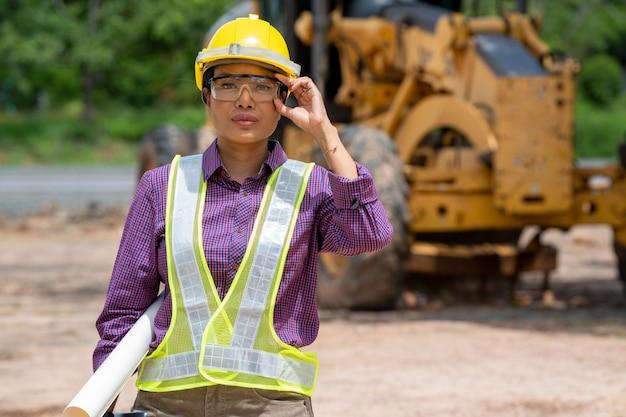 Weiblicher bauingenieur oder architekt mit gelbem helm, der mit bulldozer-lkw auf der baustelle steht.