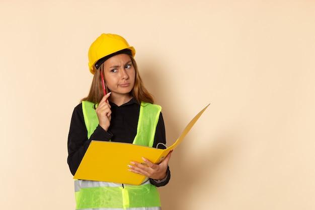 Weiblicher baumeister der vorderansicht im gelben helm, der gelbe datei hält, notizen notiert und auf weißer wand denkt