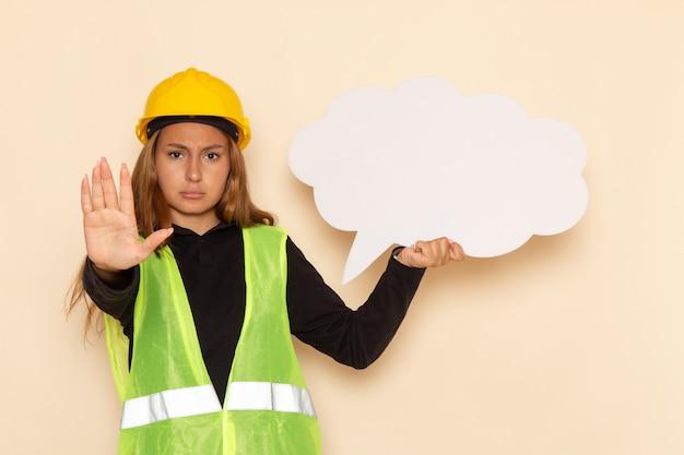 Weiblicher baumeister der vorderansicht im gelben helm, der weißes zeichen auf weißer wand hält