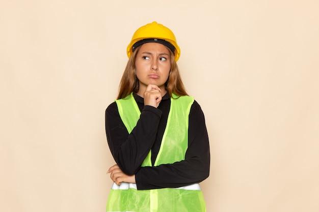 Weiblicher baumeister der vorderansicht im schwarzen hemd des gelben helms, das denken auf der weißen wand aufwirft