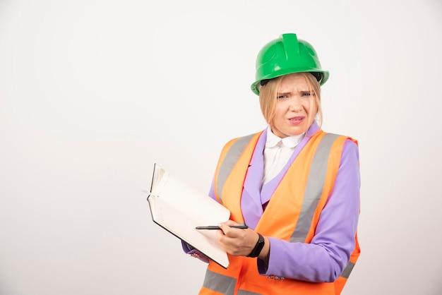 Weiblicher baumeister im helm mit tablette auf weißem hintergrund. hochwertiges foto