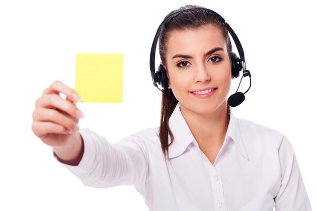 Weiblicher bediener, der gelbe note hält