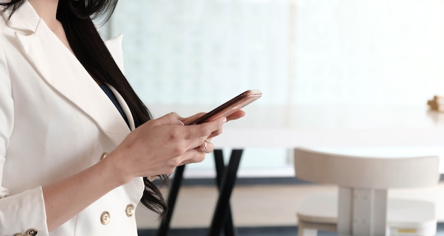 Weiblicher benutzer, der smartphone hält, das video sieht, spiel spielt, einkauft, in der mobilen technologieanwendung chattet.