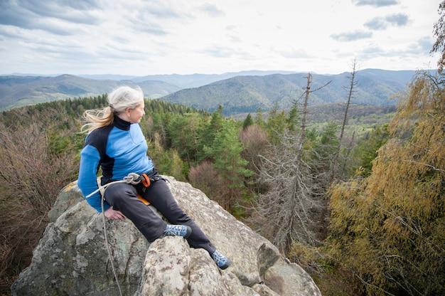 Weiblicher bergsteiger auf der spitze des felsens mit kletternder ausrüstung