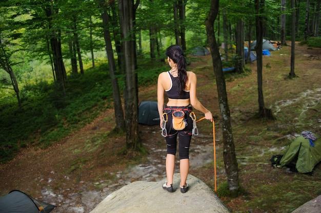 Weiblicher bergsteiger, der auf großem natürlichem flussstein im wald steht