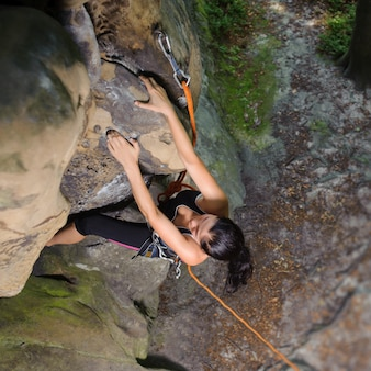 Weiblicher bergsteiger, der großen flussstein in der natur mit seil klettert