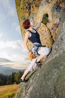 Weiblicher bergsteiger, der mit seil auf einer felsigen wand klettert